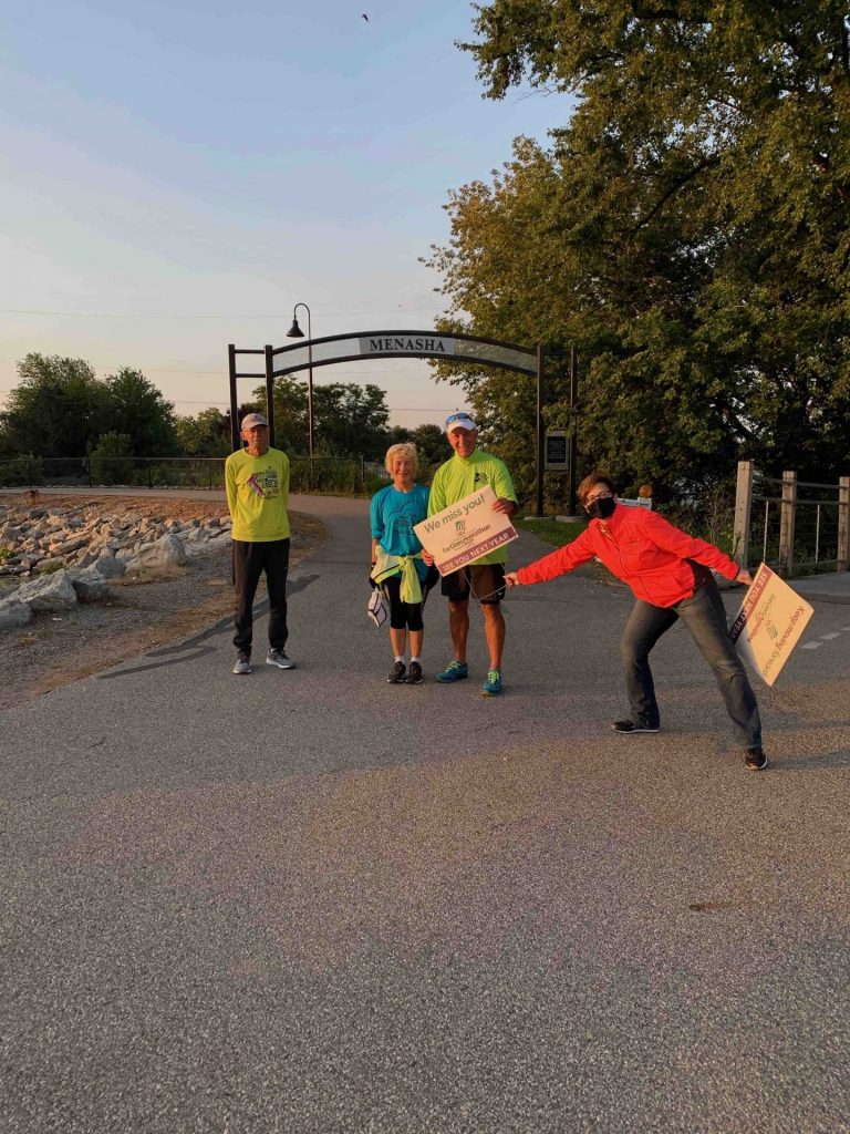 Runners smile after surprised with cheering along trail leading up to the Trestle Trail Bridge in Menasha.