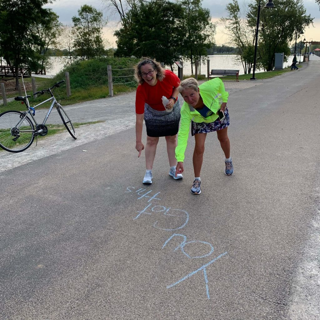Runners stop to check out sidewalk chalk messages at Fritse Park in Fox Crossing.