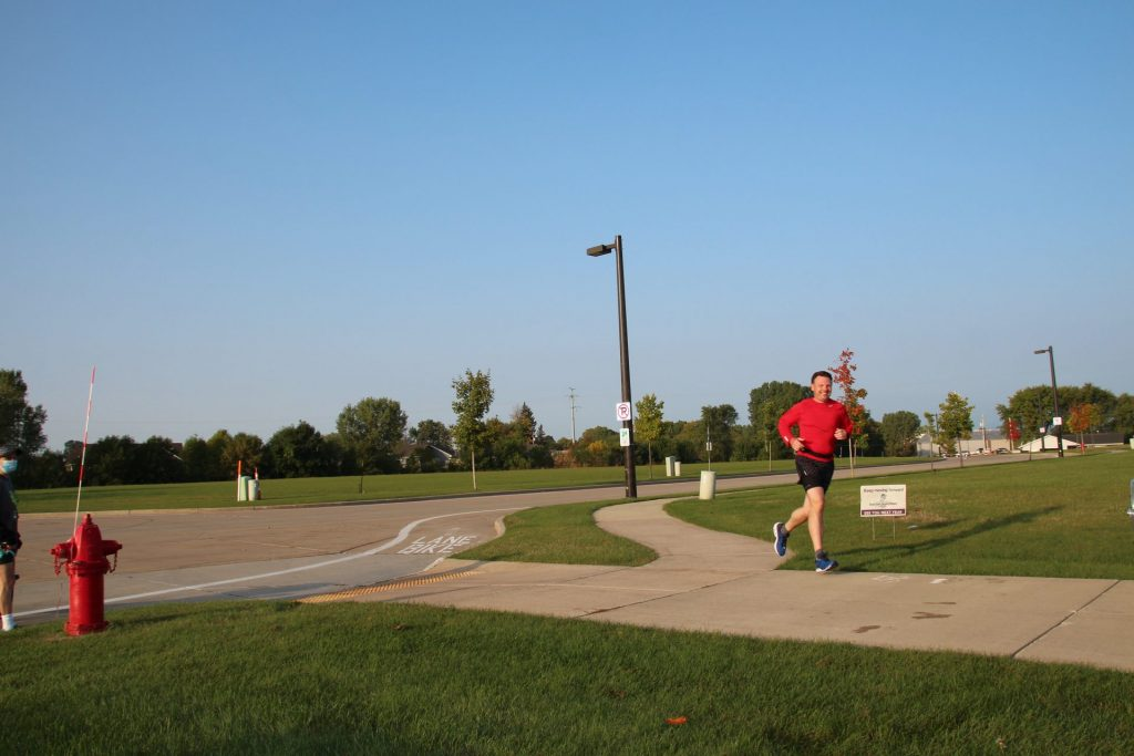 A pop-up Cheer Volunteers encourages a runner along the CE Trail